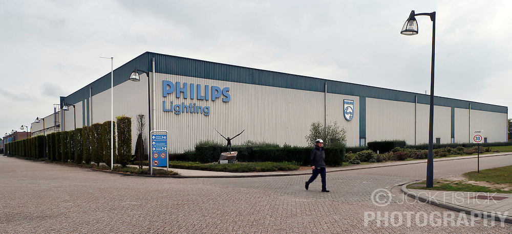 An employee walks past one of the main buildings at the Philips Lighting factory campus, in Turnhout, Belgium, on Friday, Oct. 15, 2010. (Photo © Jock Fistick)