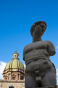 A statue in Piazza Bellini with the dome of San Giuseppe dei Teatini, Palermo, Italy