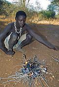 Hadzabe bushman making up a fire. Lake Eyasi, northern Tanzania.