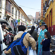 Cholita wrestler Yolanda La Amorosa  awaits for a bus with her daughter Adriana after collecting her from school in La Paz, Bolivia. Yolanda is part of the 'Titans of the Ring' wrestling group who perform every  Sunday at El Alto's Multifunctional Centre. Bolivia. The wrestling group includes the fighting Cholitas, a group of Indigenous Female Lucha Libra wrestlers who fight the men as well as each other for just a few dollars appearance money. El Alto, Bolivia, 17th March 2010. Photo Tim Clayton