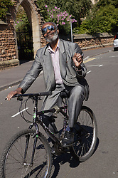 Elderly Man wearing sunglasses and smart suit; cycling and waving,
