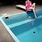 young woman 20's, sitting on a diving board above a residential swimming pool, testing water, at night.