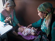Watching over a new born baby. Life inside the train - mostly Muslim Uighur people  ride this train.