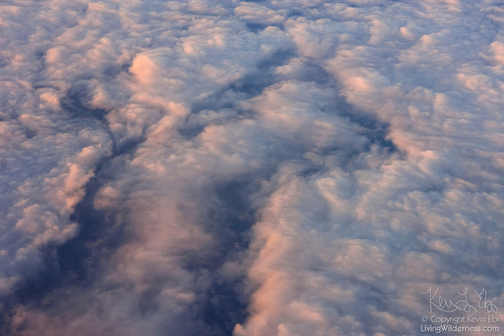 The north Atlantic Ocean is visible in a narrow break in a band of stratocumulus clouds in this aerial view captured between Greenland and Iceland.