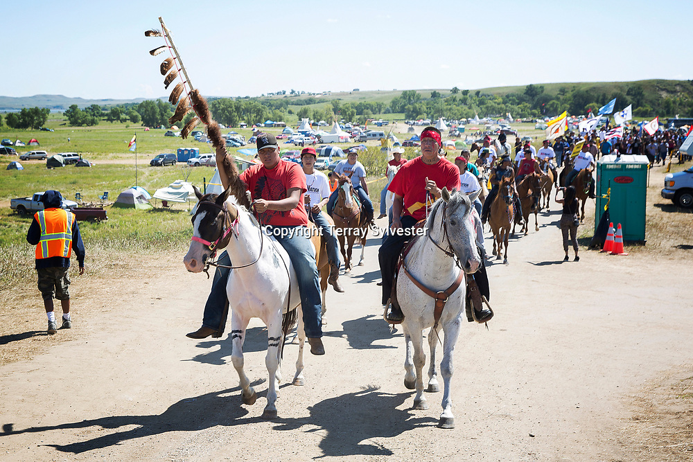 Riders lead opponents of the Dakota Access oil pipeline out of their camp and toward the pipeline route during a protest and prayer march on August 27, 2016. Cannon Ball, North Dakota, United States.