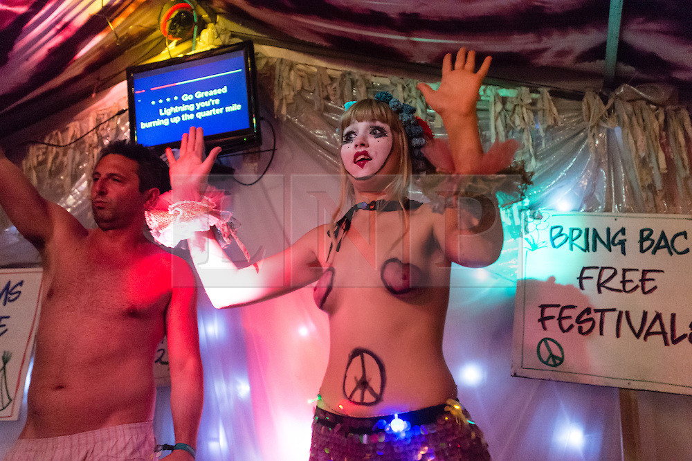 © Licensed to London News Pictures. 27/06/2015. Pilton, UK.  Night-time festival atmosphere at Glastonbury Festival 2015 in the Shangri-La area of the festival - a festival goer strips to his underwear on stage at the Kamikaze Karaoke bar, egged on by a male performer in drag with fake breasts alongside topless female performers.  On Saturday Day 4 of the festival.  Shangri-La is a destroyed dystopian pleasure city.  This years headline acts include Kanye West, The Who and Florence and the Machine, the latter being upgraded in the bill to replace original headline act Foo Fighters. Photo credit: Richard Isaac/LNP