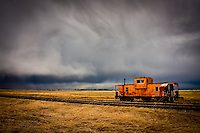 A vintage caboose sits on its tracks with the dramatic clouds of a brewing storm behind it.<br /> <br /> <br /> <br /> ©2009, Sean Phillips<br /> http://www.Sean-Phillips.com