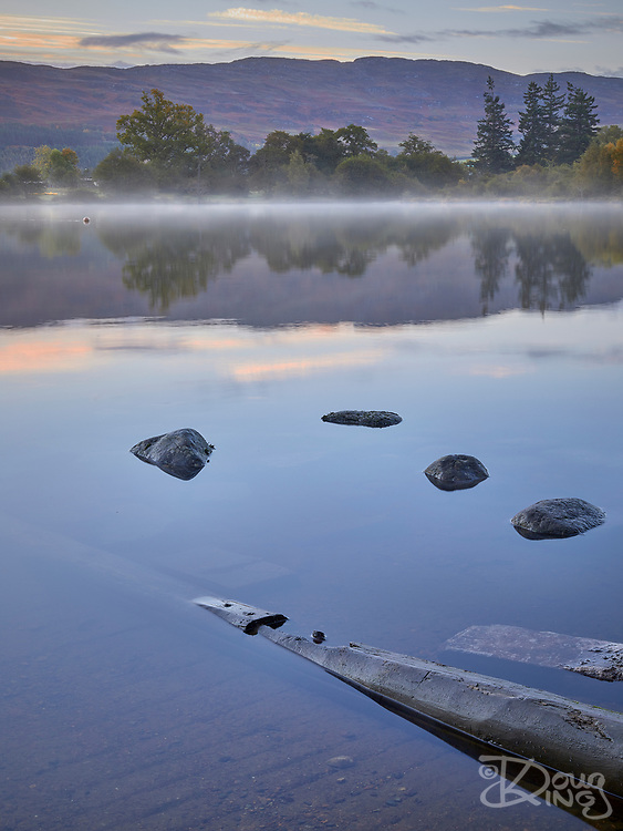 Dawn mist lingers over the still waters of Loch Ness with scattered rocks breaking the surface