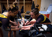 Sam Javanbakht and Olivia Karas of the Michigan Wolverines help wrap the ankle of Emma McLean in the locker room before the Elevate the Stage meet at the Huntington Center ON February 23, 2019 in Toledo, Ohio.