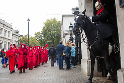 London, UK. 7 October, 2019. Red Brigade climate activists from Extinction Rebellion march past Horseguards on the first day of International Rebellion protests to demand a government declaration of a climate and ecological emergency, a commitment to halting biodiversity loss and net zero carbon emissions by 2025 and for the government to create and be led by the decisions of a Citizens' Assembly on climate and ecological justice.