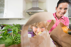 Boy helping his mother with grocery bags in kitchen, Bavaria, Germany
