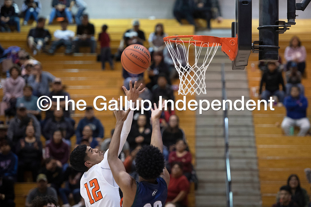 Gallup's Isaac Bustinza (12) and Rio Rancho's Miguel Baray (23) reach for a rebound at Gallup High School Tuesday night in Gallup.