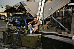 A U.S. soldier from the 1st AD rests at the site of the explosion at the Canal Hotel in Baghdad, Iraq on Aug. 21, 2003. The previous day a cement truck packed with explosives detonated outside the offices of the UN headquarters in Baghdad, Iraq, killing 20 people and devastating the facility in an unprecedented suicide attack against the world body. At least 100 people were wounded.