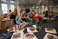 DEU, Deutschland, Germany, Berlin, 13.08.2015: Helfer packen Säcke, die ein Begrüßungsset für neuankommende Flüchtlinge beinhalten (Kopfkissen, Bettwäsche, Handtücher) in der kurzfristig eingerichteten Notunterkunft im Berliner Stadtteil Karlshorst. Die vom DRK betriebene Erstaufnahmestelle in der Köpenicker Allee soll die Zentrale Aufnahmeeinrichtung für Asylbewerber der LaGeSo in Moabit entlasten.
