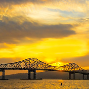 The golden setting sun creates a dazzling glow over the Hudson river valley silhouetting the Tappan Zee bridge.