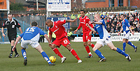 Junior Agogo (centre) attacks for Nottingham Forest.  Chesterfield defenders (left) Aaron Downes & (right) Derek Niven