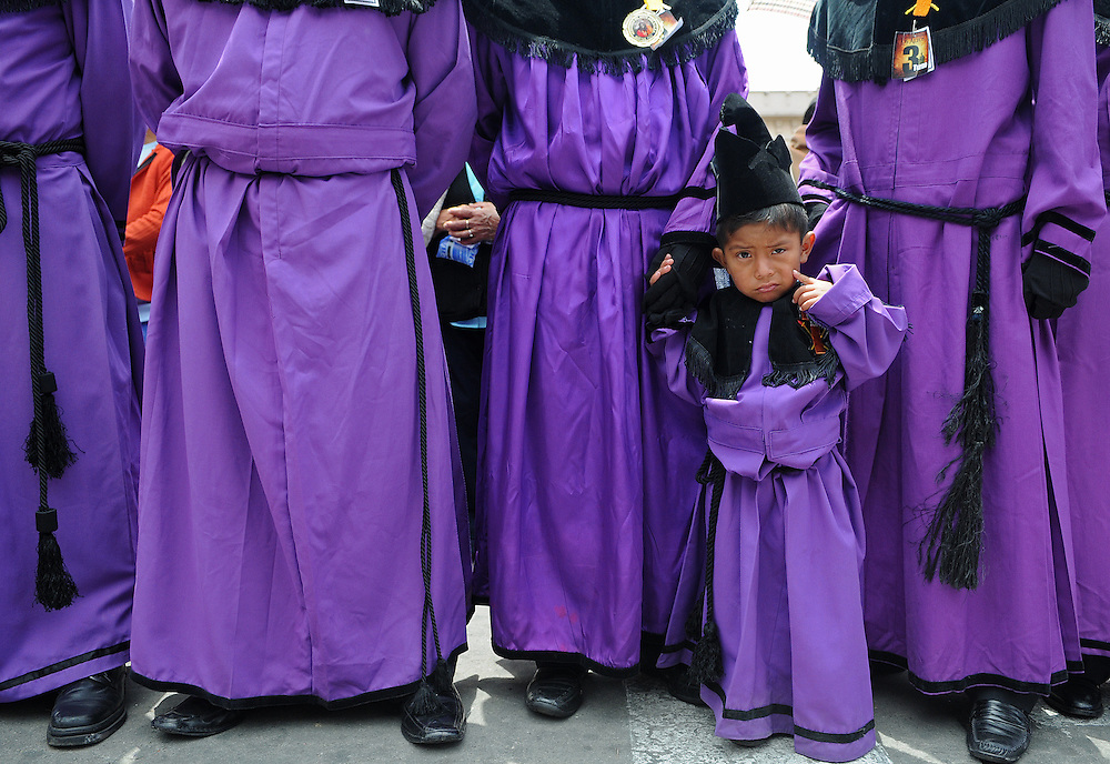 """Apr 22, 2011 - Quetzaltenago, Guatemala - Semana Santa or Holy Week continued in Quetzaltenago with the """"Procession to the Cathedral"""" Resident of the second largest city in Guatemala lined the streets of the Procession route leading into the Central Park. A small boy accompanies other memebers of the Nazarene Brotherhood during the procession Friday Morning..(Credit Image: © Josh Bachman/ZUMA Press)"""