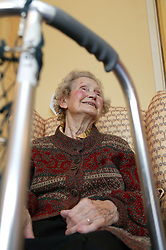 View through walking frame of older woman at home,