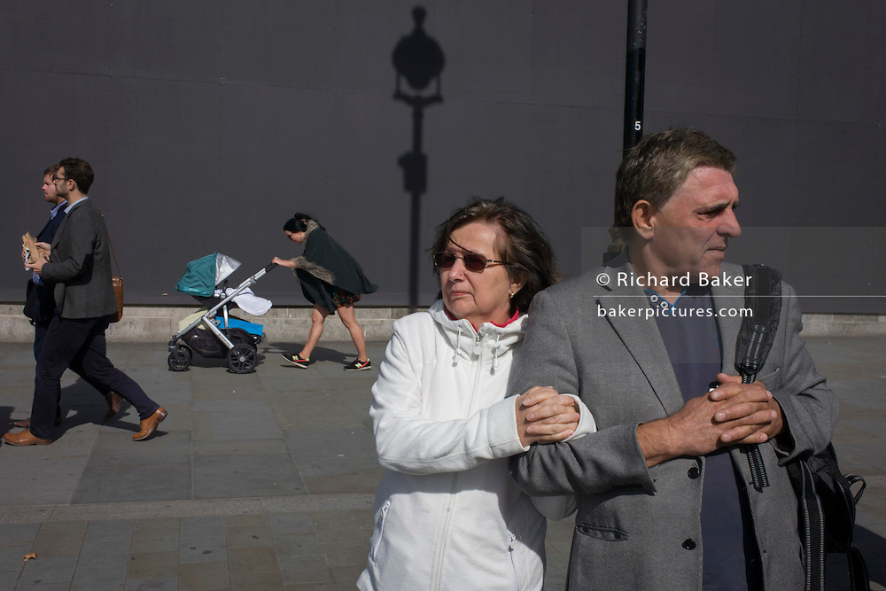 Couple arm in arm with young mother against a grey construction hoarding in central London's Trafalgar Square.