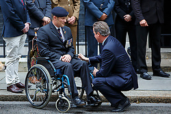 © Licensed to London News Pictures. 22/10/2015. London, UK. Prime Minister David Cameron meets Alex Noble before buying a Royal British Legion poppy in Downing Street, London on Thursday, 22 October 2015. Photo credit: Tolga Akmen/LNP