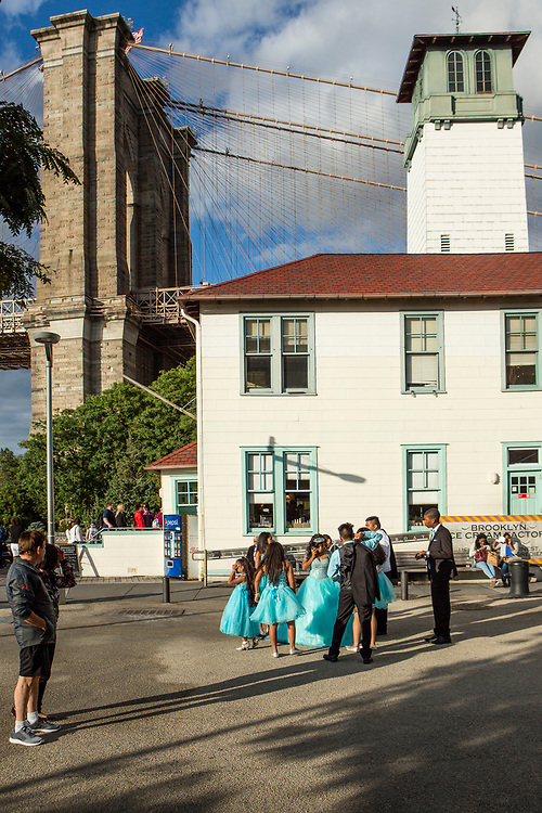Brooklyn, NY - 9 September 2017. Girls in bright party dresses celebrate a quinceañera at the Brooklyn Ice Cream Factory on Pier 1 of Booklyn Bridge Park. The ice cream shop is in a converted fireboat house just south of the Brooklyn Bridge.