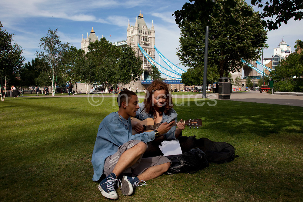 Two friends practice their music together in Potters Fields, a green space and part of More London. More London is a new development area where over the last few years of construction has resulted in a new office and business space of modern architecture. The buildings, close to each other, provide labyrinthine walkways for the workers who contain them. There are open communal areas for people to sit, and green areas likewise.