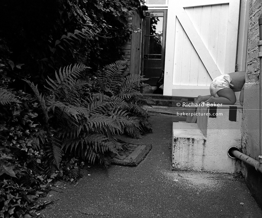 """On all fours."" An eleven month-old infant crawls up some back garden steps and into her parents' house. Her head and shoulders are already hidden as she disappears inside. She is exploring a familiar world, being bold, gaining strength and confidence to move independently to eventually stand upright and walk unaided. Someone has taped a short stick to the upper step to help her position herself downwards when exiting the house backwards.  Wearing only a nappy (diaper) it is clearly a warm summer's day. This is from a documentary series of pictures about the first year of the photographer's first child Ella. Accompanied by personal reflections and references from various nursery rhymes, this work describes his wife Lynda's journey from expectant to actual motherhood and for Ella - from new-born to one year-old."
