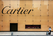 A woman stands by a large Cartier display outside a high-end shopping mall in Shanghai, China, on October 01, 2011. China is by far the world's fastest growing market for luxury brands.