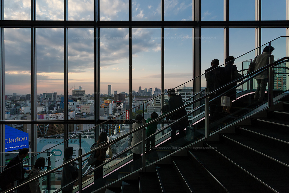 People  on an escalator in front of the Tokyo skyline from Hikarie Tower, Shibuya, Tokyo, Japan. Friday April 28th 2017