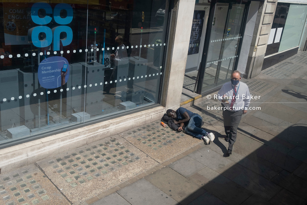 A wealthier man carrying his lunch, walks past a black male lying on the pavement outside a branch of the Co-Op bank on the Strand, on 23rd June 2021, in Westminster, London, England.