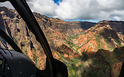"""Waimea Canyon State Park, seen via helicopter on island of Kauai, Hawaii, USA. Waimea Canyon (""""the Grand Canyon of the Pacific"""") slices as much as 3000 feet deep across ten miles of western Kauai. About 4 million years ago, a catastrophic collapse of the volcano that created Kauai created a fault which was gradually cut deeper by the Waimea River, fed by extreme rainfall on the island's central peak, Mount Wai'ale'ale, among the wettest places on Earth. Waimea is Hawaiian for """"reddish water,"""" referring to the local orange clay. This image was stitched from multiple overlapping images."""