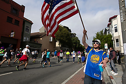 A man waves an American flag as he cheers on the participants at the 107th running of the Bay to Breakers, Sunday, May 20, 2018, in San Francisco. (Photo by D. Ross Cameron)