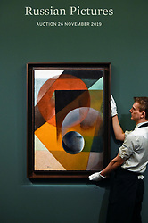 """© Licensed to London News Pictures. 22/11/2019. LONDON, UK. A technician presents """"Spherical Suprematism"""", first half of the 1920s, by Ivan Kliun (Est. GBP2.5-3.5m) at the preview for the upcoming sales of Russian artworks at Sotheby's New Bond Street.  The Russian Pictures and Works of Art, Fabergé and Icons sales take place on 26 November.  Photo credit: Stephen Chung/LNP"""