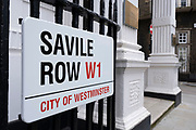 Street sign for Savile Row on 5th March 2021 in London, England, United Kingdom. Savile Row is a street in Mayfair, central London. Known principally for its traditional bespoke tailoring for men.