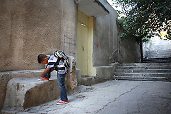 Iraqi refugee Hussein Thamer, 8, ties his shoe on his way to the first day of school in Amman, Jordan, Aug. 19, 2007. His family fled the violence in Baquba, Iraq two years ago and are waiting for asylum from the U.N. Refugee Agency so they can finally make a permanent home.