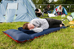 © Licensed to London News Pictures. 25/06/2015. Pilton, UK. Festival campsite atmosphere at Glastonbury Festival 2015 on Thursday Day 2 of the festival. A new arrival who arrived in the early hours aleep on an inflatable mattress in the campsite.  This years headline acts include Kanye West, The Who and Florence and the Machine, the latter having been upgraded in the bill to replace original headline act Foo Fighters.   Photo credit: Richard Isaac/LNP