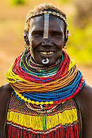 Nyangatom tribe woman wearing layers of beaded necklaces as decoration. They also wear pieces of watch strap as ornamentation. Omo Valley, Ethiopia.