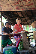 """A touris woman """"works"""" with others to pound cooked rice so that it can be pressed into noodles."""