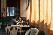 A couple sit and talk Customers in the Indian Coffee House in Nagpur, India, shielded by thick curtains from the afternoon sun. The Indian Coffee Houses are a national chain of worker-owned cafes that were integral to Indias pre and post Indepence movements.
