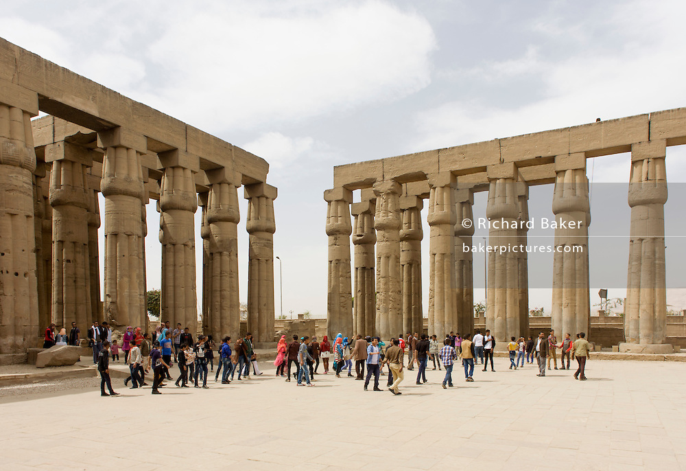 Tourist groups stand and photograph beneath the giant columns in the Solar Court of Amenhotep III, at the ancient Egyptian Luxor Temple, Nile Valley, Egypt. The temple was built by Amenhotep III, completed by Tutankhamun then added to by Rameses II. Towards the rear is a granite shrine dedicated to Alexander the Great and in another part, was a Roman encampment. The temple has been in almost continuous use as a place of worship right up to the present day.