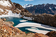 """Ice partially covers an unnamed lake below Paso Quadrado, near El Chalten, Santa Cruz Province, Argentina, Patagonia, South America. The snowy peak of Cerro Gorra Blanca and conjoined Cerro Neumayer rise behind the ridge of Cerro 30 Aniversario. Initially, we hiked the scenic Rio Electrico Valley to Refugio Piedra del Fraile (""""Stone of the Friar"""", 14.5 km round trip) for an overnight stay in a 4-person dorm room supplied with pads. From the refuge, a path ascends very steeply to Paso Quadrado (gaining 1340 m vertically in 8.4 km round trip) for a spectacular view south. We ascended glacier-carved orange rocks to reach Paso Quadrado. The last kilometer climbs up steep snow which could require crampons if icy. Views keep improving the higher you go."""