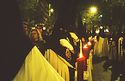 """Unknown brotherhood at night with candles, Seville, Andalusia, Spain...Semana Santa de Sevilla, Catholic Holy Week from Palm Sunday to Easter Sunday, is one of the most important traditional, cultural and spiritual events in Seville. The origins of the penitential Holy Week in Seville are to be found in the late Middle Ages. At the heart of Semana Santa are the brotherhoods (Hermandades y Cofradias de Penitencia).  At the centre of each procession are the pasos, an image or set of images set atop a movable float of wood. When a brotherhood has three pasos, the first one would be a sculpted scene of the Passion or an allegorical scene, known as a misterio (mystery); the second an image of Christ and the third an image of the Virgin Mary known as a dolorosa. Many sculptures are of great antiquity and considered artistic masterpieces. A total of 60 penitential processions are organized by hermandades and cofradías, religious brotherhoods. Members precede the pasos dressed in penitential robes and hoods. Sometimes accompanied by brass bands. They take designated routes from home churches and chapels to the Cathedral and back again. Improvised flamenco songs """"saetas"""" are sung to the processions from balconies. The marchers are often accompanied by brass bands, cappella choirs, or a drum and trumpet (historical traditions for a poorer neighborhood)"""