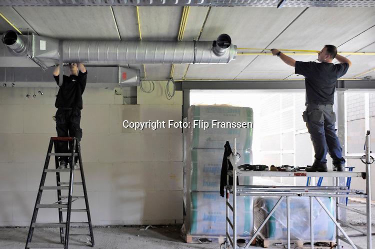 Nederland, Ubbergen, 23-9-2010 Nieuwbouw van middelbare school, Havo Notre Dame. Een bouwvakker, installateur, werkt aam het ventilatiesysteem . Foto: Flip Franssen/Hollandse Hoogte