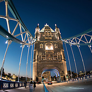 London's famous Tower Bridge at dusk. Constructed in the late 1800s, the ornate Tower Bridge is one of London's iconic landmarks. It gets its name from the nearby Tower of London on the northern bank of the River Thames.