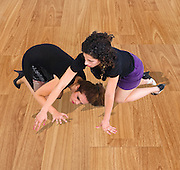 Two young female friends searching for a contact lens on a wooden floor