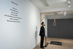 "© Licensed to London News Pictures. 13/11/2018. LONDON, UK. The artist's poerty on a wall next to a staff member, posing as a prison guard, and the hangman's noose.  Preview of ""Glad I Did It"", a new work by Irish artist Christina Reihill at Bermondsey Project Space.  The interactive artwork looks at the life and death of Ruth Ellis, the last woman to be hanged in Britain, after she shot her lover, racing driver, David Blakely in 1955.  On display are the artist's interpretation of Ruth Ellis' prison cell, including furniture and props, the hanging room together with a video display of the artist in conversation.   The show runs 14 November to 1 December 2018.  Photo credit: Stephen Chung/LNP"