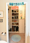 Beyond the master bathroom is a walk-in closet and shown are shelves holding Rikki Glen's boot collection. Sheridan and Rikki Glen are At Home in their Tanglewood subdivision home in Caseyville, IL on Wednesday January 16, 2019. <br /> Photo by Tim Vizer