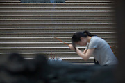 A woman praying and burning incense in the Jing'an Temple courtyard , Shanghai, China