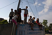 Nepalese children playing outdoors on the streets in Kathmandu, Nepal.  They have climbed up into the wall using the electricity pylon pole.