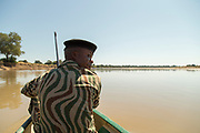 National Park guard on boat on river, South Luangwa National Park, Zambia
